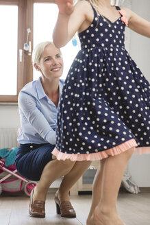 Businesswoman watching her little daughter dancing at children's room - MIDF000779