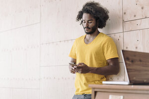 Young man leaning against wooden wall using cell phone - RIBF000424