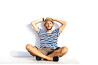Vacationer with straw hat and striped t-shirt sitting on spur leaning against white wall - GEMF000927
