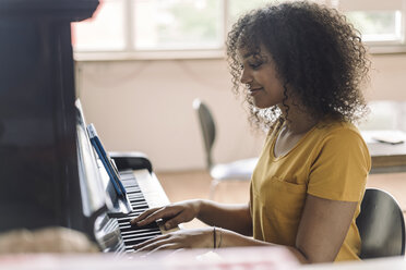 Young woman playing piano, reading notes from digital tablet - RIBF000435