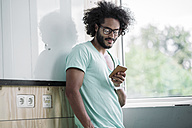 Young man in office using smart phone - RIBF000477