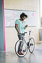 Young man with bicycle using smart phone - RIBF000480