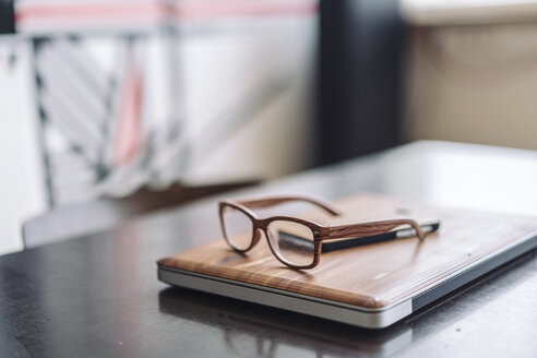 Wooden laptop and wooden glasses on desk - RIBF000498