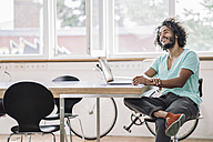 Young designer sitting in office using laptop - RIBF000531