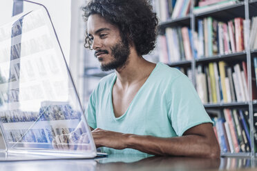 Young man working in library, using futuristic computer - RIBF000534