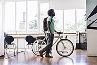 Young man with rucksack pushing bicycle in office - RIBF000540