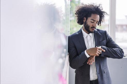 Young businessman using smartwatch - RIBF000573