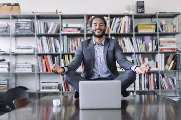 Young businessman sitting in office meditating in front of laptop - RIBF000579
