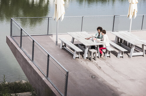 Two businesswomen sitting on terrace looking at laptop, seen from above - UUF008166