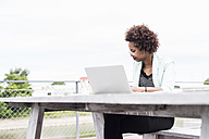 Pensive businesswoman with laptop working outside - UUF008175