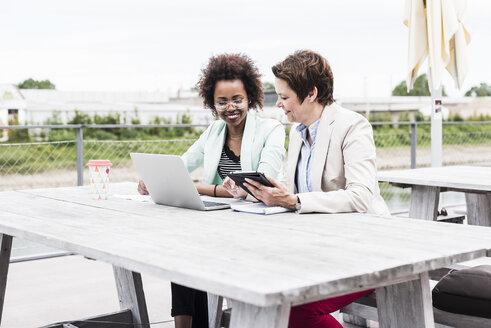 Two businesswomen working on terrace - UUF008178