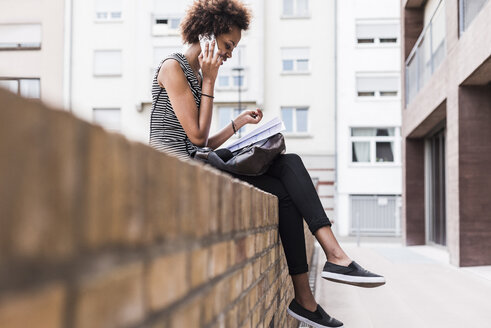 Young woman sitting on wall telephoning with cell phone - UUF008199