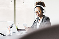 Businesswoman with headphones sitting at desk looking at cell phone - UUF008232
