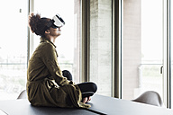 Woman in office sitting on conference table wearing virtual reality glasses - UUF008262