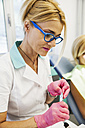Orthodontist adjusting braces - ZEDF000224