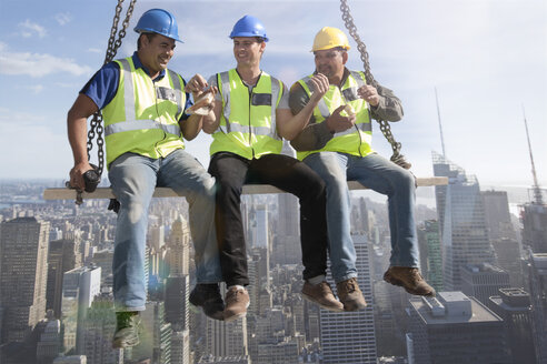 Three construction workers sitting on suspended scaffolding high above city having lunch - ZEF009161