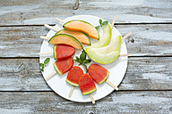 Plate of homemade watermelon ice lollies, slices of Galia and Cantaloupe melon - MAEF011914