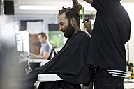 Barber combing and cutting hair of a customer - ZEF009203