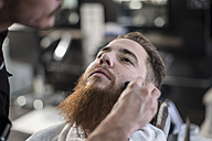 Barber brushes customers side hairs at barbershop - ZEF009221