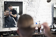 Barber and customer, barber combs his hair - ZEF009224