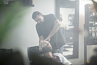 Customers hair been washed as barber, gently washes his hair - ZEF009230