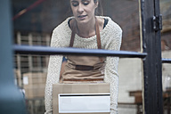 Young woman picking up cardboard box - ZEF009239