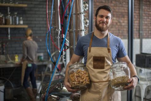 Smiling man holding jars in distillery - ZEF009257
