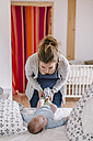 Mother and baby boy, lying on bed, dressing - HAPF000656