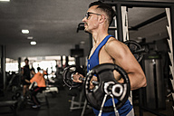 Man lifting barbell in gym - JASF000994
