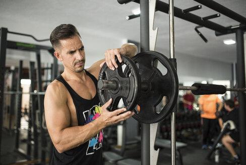 Man preparing to train with fitness bar - JASF000997