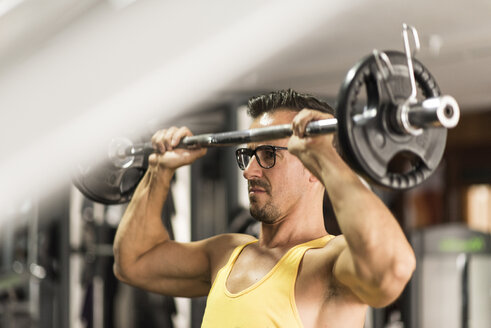 Man lifting barbell in gym - JASF001000