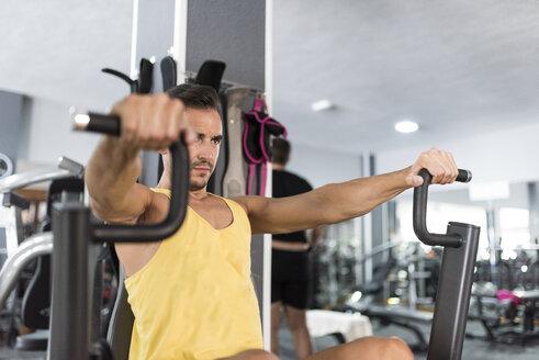 Man exercising at pectoral pull machine in gym - JASF001003