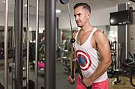 Man exercising at pull machine in gym - JASF001006