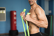 Man exercising with resistance band in gym - JASF001009