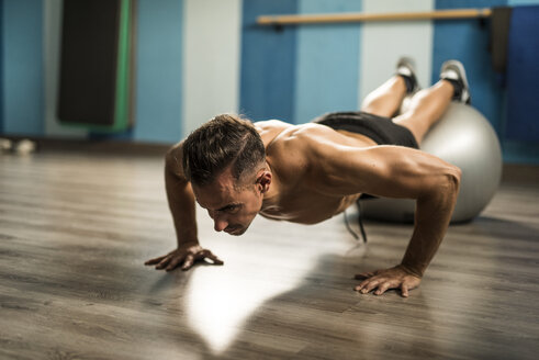 Man doing push-ups with fitness ball in a gym - JASF001012