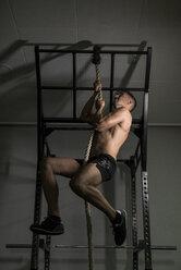 Man climbing rope at power rack - JASF001015