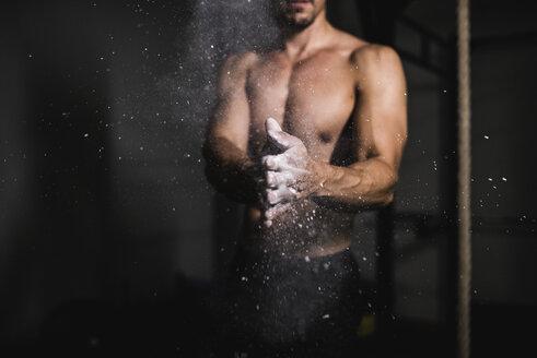 Athlete applying chalk on his hands - JASF001021