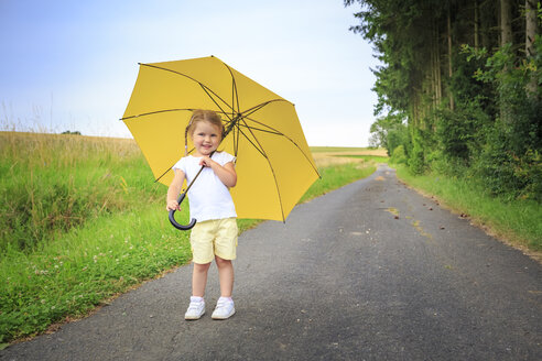 Smiling little girl with yellow umbrella standing on country road - VTF000539