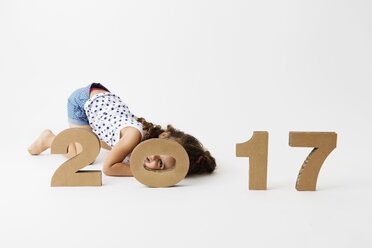Smiling little girl playing with cardboard numbers forming the date '2017' - LITF000399