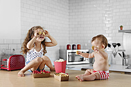Little girl covering her eyes with cookies - LITF000405