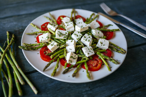 Plate of green asparagus, tomato slices and diced sheep cheese on  wood - KIJF000602
