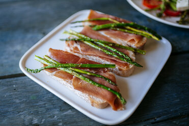 Bread slices with cured ham and grilled green asparagus on platter - KIJF000608