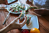 Woman's hand holding bread slice with cured ham and grilled green asparagus - KIJF000611