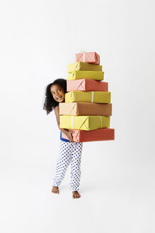 Smiling little girl holding a pile of wrapped gifts - LITF000425