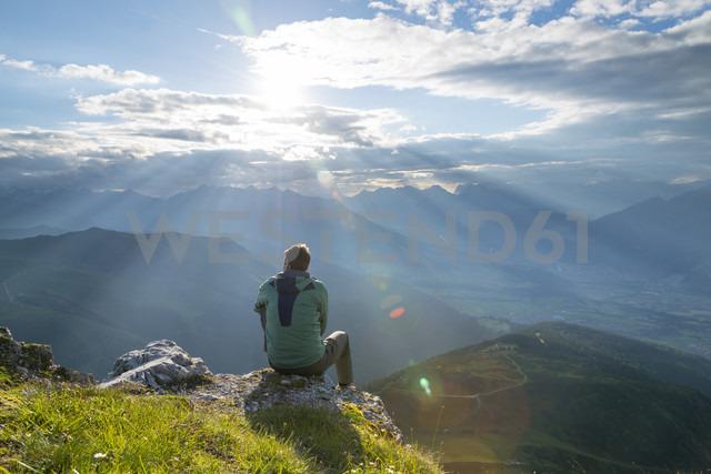 Austria, Tyrol, hiker sitting on viewpoint against the sun - MKFF000314