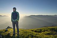 Austria, Tyrol, hiker standing on meadow at sunrise - MKFF000320
