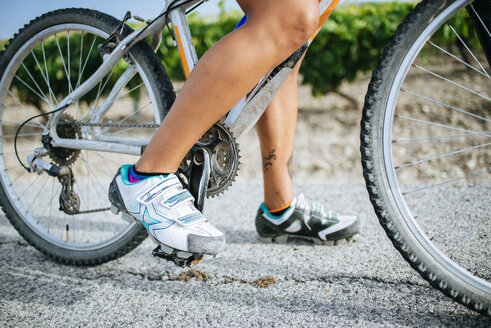 Close-up legs of female cyclist with cycling shoes - KIJF000617