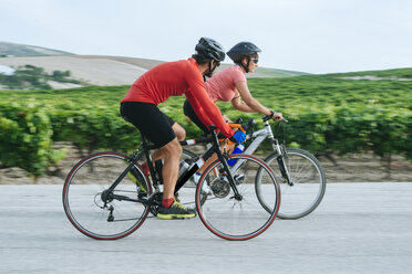 Spain, Andalusia, Jerez de la Frontera, Couple on bicycles on a road between vineyards - KIJF000620