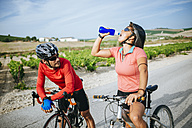 Spain, Andalusia, Jerez de la Frontera, couple of bikers drinking water on a rural road between vineyards - KIJF000623