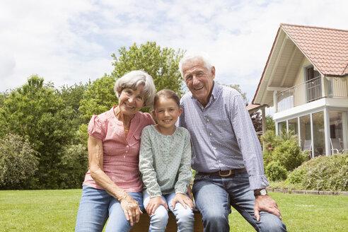 Portrait of happy grandparents with granddaughter in garden - RBF004755